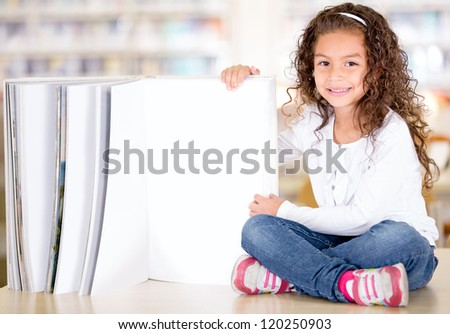 Little girl with an open book at the library