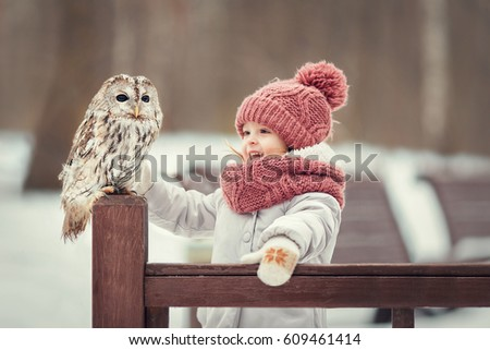 Stock Photo Little girl with an owl in the forest in winter
