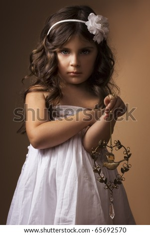 Little girl with antique copper toy. Low key.