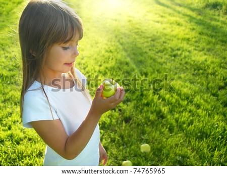 Little girl with apple in the garden