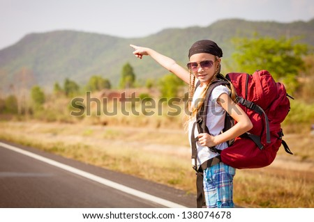little girl with backpack standing on the road and showing on mountain
