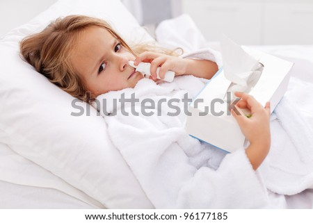 Little girl with bad cold in bed - using nasal spray and paper napkins