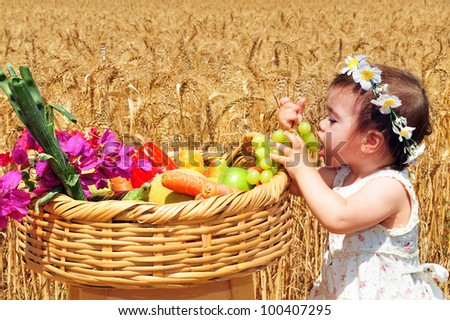 Little girl with basket of the first fruits during the Jewish holiday, Shavuot in Israel.