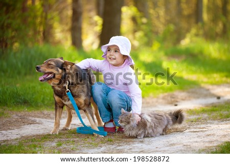 Little girl with big dog and cat in the forest