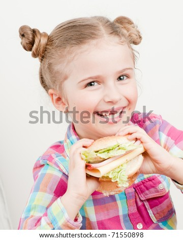 Little girl with big sandwich - stock photo