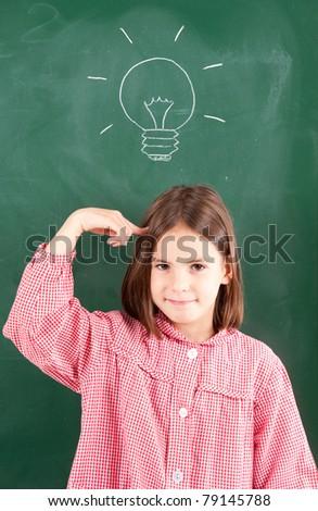 little girl with blackboard and lightbulb over her head - stock photo