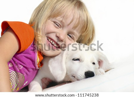 Little girl with blond hair plays with white pup on a white background.