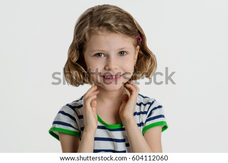 Little girl with blond hair smiling at the camera. Photo taken in studio on a white background.