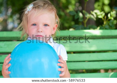 Little girl with blue air balloon sitting o bench