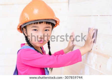 Little girl with carpenter work talent with sanding on wood