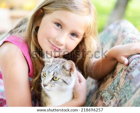 Little girl with cat. Outdoors.