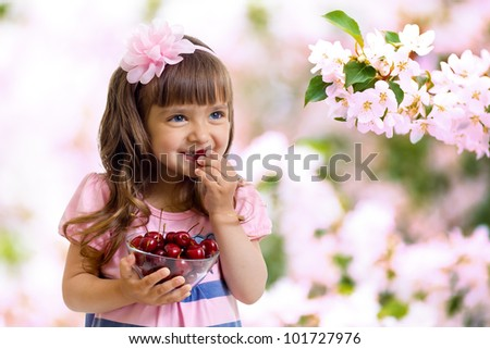 little girl with cherry berries bowl in garden