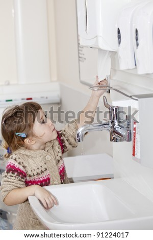 little girl with clean hands grabbing paper towel