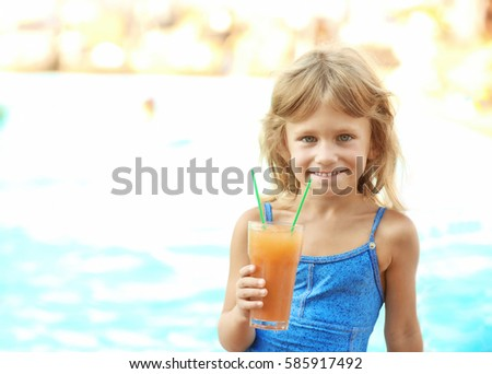 Little girl with cocktail at swimming pool on sunny day #585917492