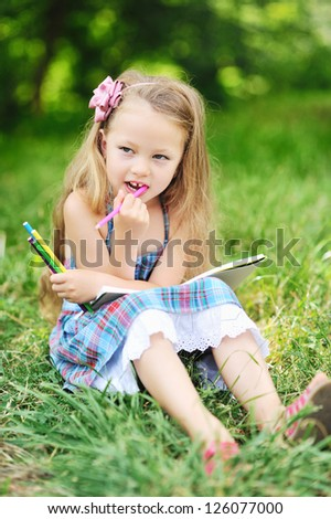 Little girl with color pencils in a park