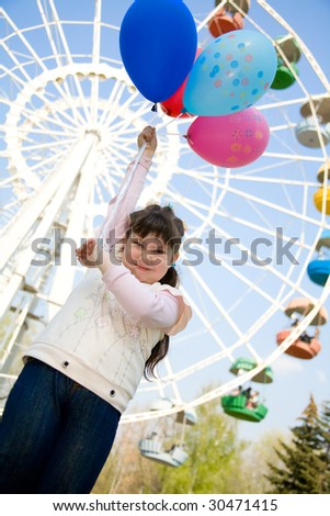 little girl with colorful balloons with ferris wheel on background