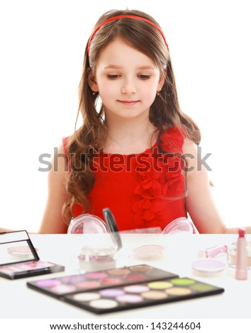 Little girl with cosmetics. Isolated  on white background.