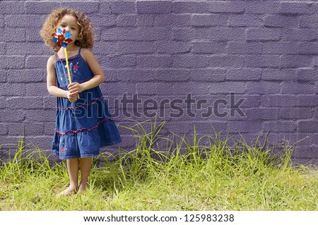 little girl with curly hair wearing a blue dress blowing a pinwheel, standing barefoot on grassy ground against a purple brick wall