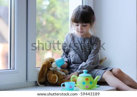 Little girl with dark hairs in gray dress with tea and bunny sitting near the window