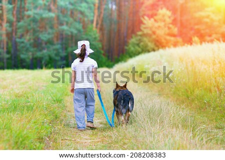 Little girl with dog walking on the dirt road back to camera
