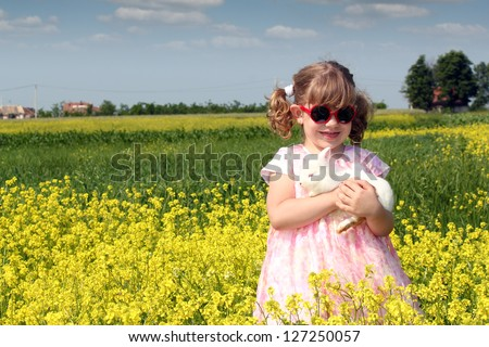 little girl with dwarf white bunny spring scene