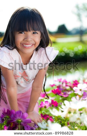 Little girl with flowers field,outdoor portrait
