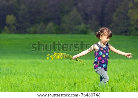 Little girl with flowers on green field