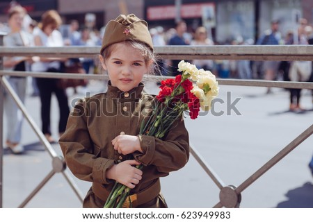 Little girl with flowers on the holiday of May 9, the day of victory in Russia #623949983
