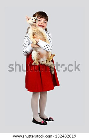 Little girl with fluffy cat in hands. Portrait on gray background