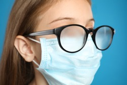 Little girl with foggy glasses caused by wearing disposable mask on blue background, closeup. Protective measure during coronavirus pandemic
