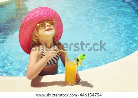 Little girl with fresh  cocktail on watter pool in the summer day #446154754