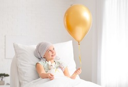 Little girl with golden balloon undergoing course of chemotherapy in clinic. Childhood cancer awareness concept
