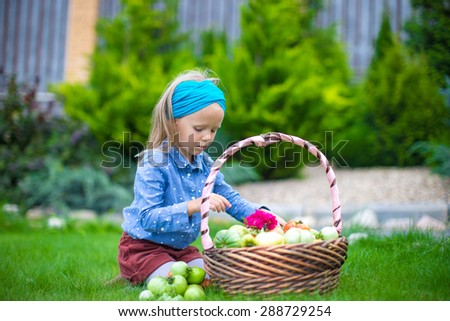 Little girl with great autumn harvest of tomatoes in baskets