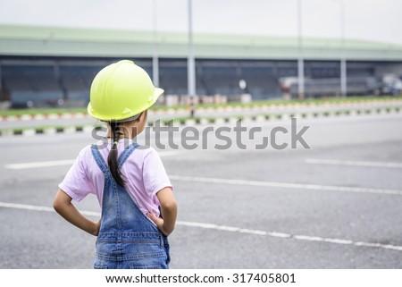 Little girl with green helmet in warehouse center background; Transportation work