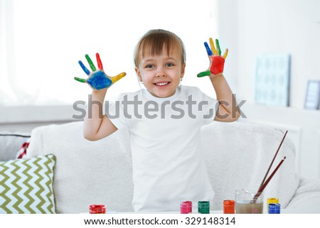Little girl with hands in paint, on home interior background
