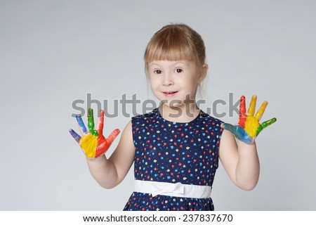 little girl with hands in paint on white