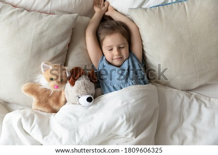 Little girl with hands stretched lying on pillow comfy mattress with fluffy stuffed toys friends cat and teddy bear animals sleep at home. Daytime nap, enough of night rest for healthy child concept Сток-фото ©