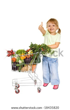 Little girl with healthy vegetables in shopping cart showing thumbs up - isolated