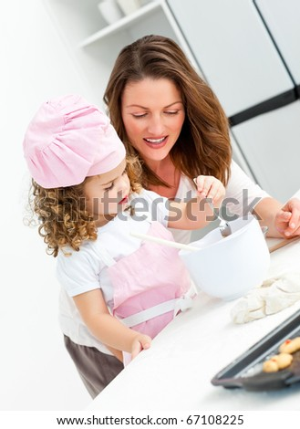 Little girl with her beautiful mother cooking together in the kitchen - stock photo