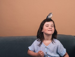 little girl with her bird of the agaporni breed playing on the sofa