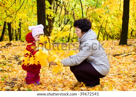 Little girl with her mother on autumn forest