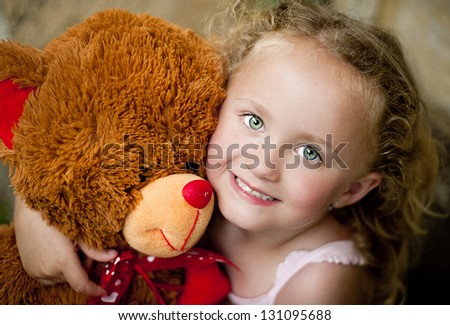 Little girl with her teddy is sitting in front of old door