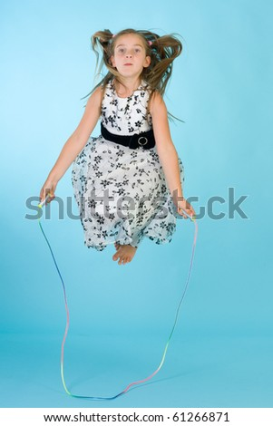 Little girl with jumping rope in midair