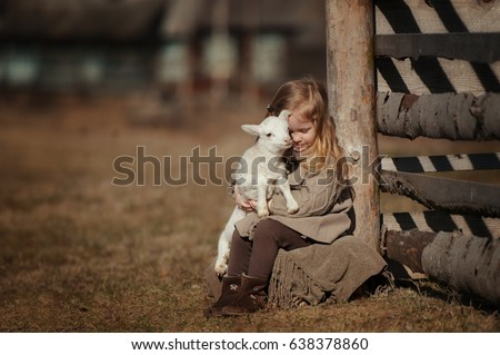 little girl with lamb on the farm. She sits by the fence and hugs the lamb. #638378860