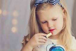 Little girl with lipstick and mirror. Makeup in studio