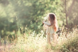 little girl with long blond hair standing in the field with bouquet of flowers in her hands at beautiful summer sunny day