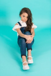 Little girl with long brunette hair in jeans overall on blue background. Fashion, style concept. Beauty, look, hairstyle. Childhood, preteen, youth, punchy pastel