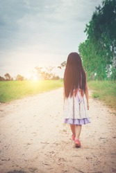 Little girl with long hair wearing dress is walking away from you down rural road.