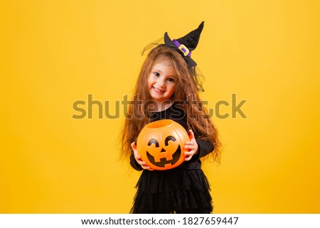 little girl with long red hair smiles in a Halloween witch costume and holds a pumpkin-shaped candy bowl on a yellow background. Halloween for children, space for text