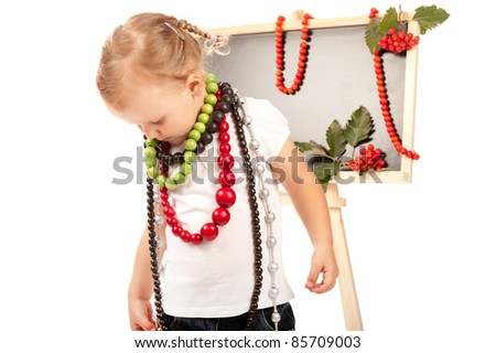 little girl with lots of corals standing in studio at the blackboard
